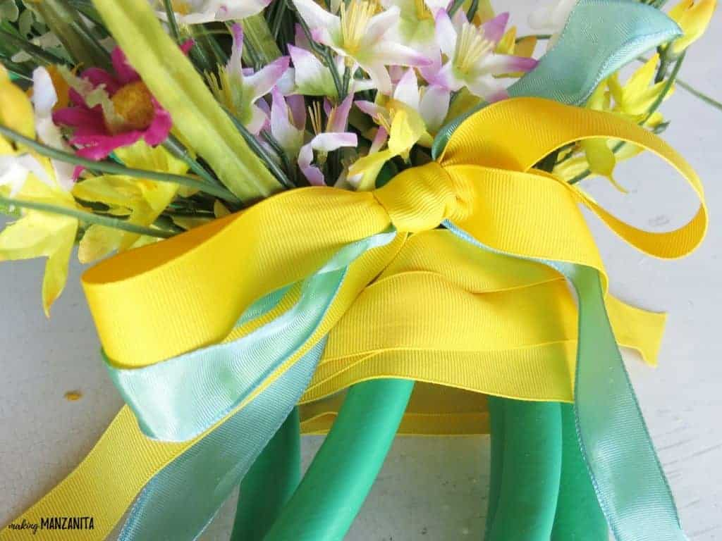 Close up shot of yellow and blue ribbon bow tied around a garden hose wreath