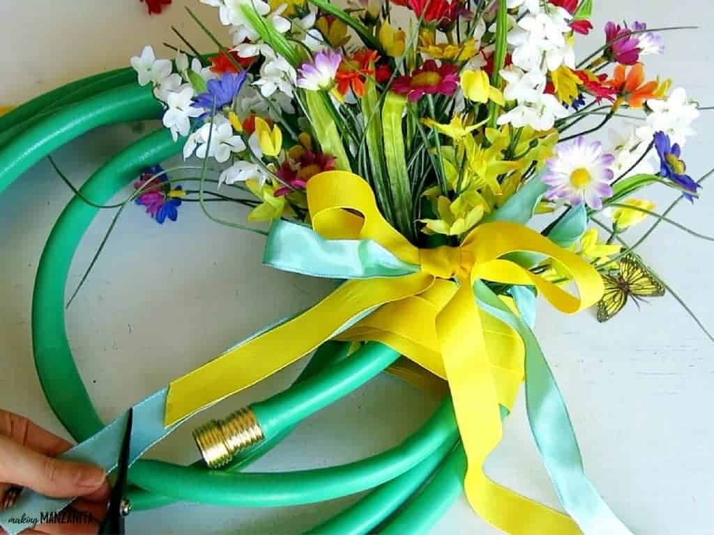 Cutting the ribbon on the front of a bow on a garden hose wreath with fake flowers