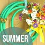 Wreath made with a garden house with fake flowers hanging on a tan door with text overlay that says summer wreath