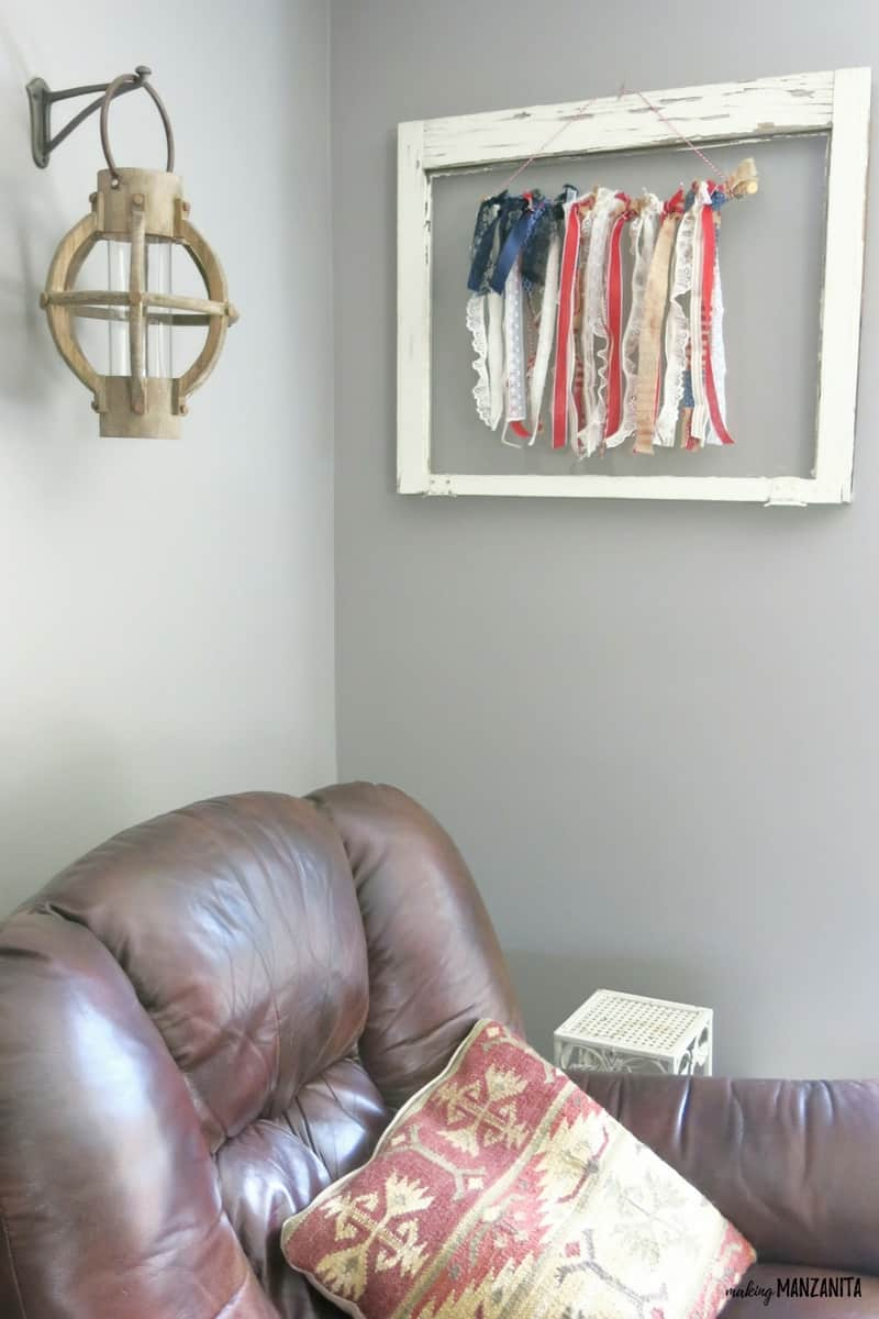 shows the ribbon flag hanging on a gray wall with a white vintage window frame around it with a brown leather recliner and white table below it and a lamp to the left of it