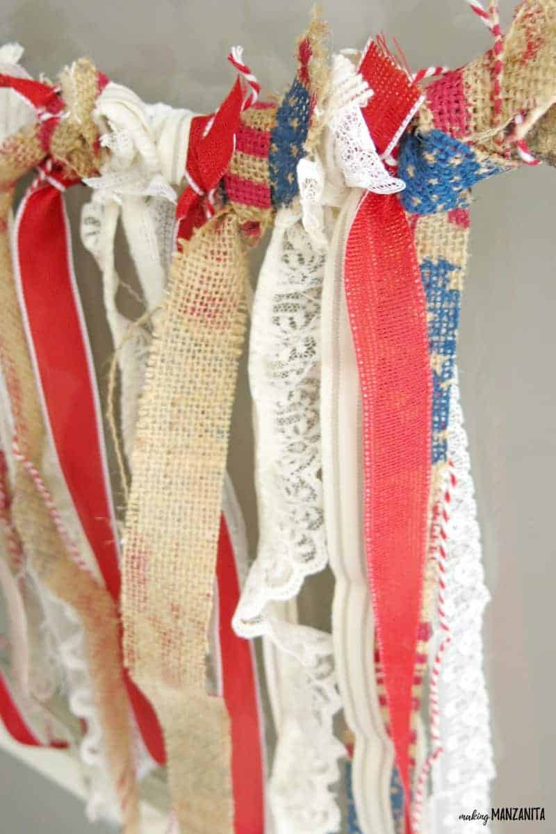 shows a view of the hanging red, white, and burlap ribbon tied to a branch