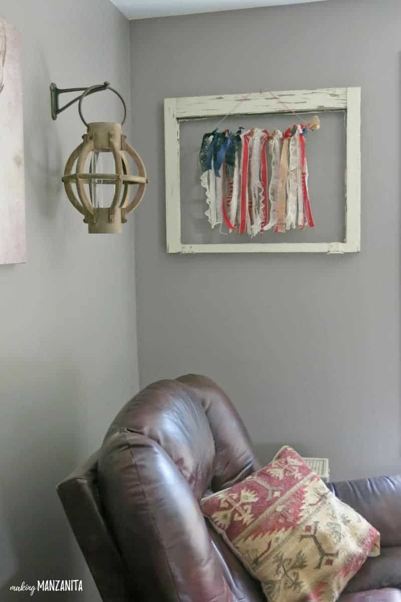 shows the ribbon flag hanging on a gray wall with a white farmhouse frame hanging around it with a brown leather recliner sitting below it and a metal lamp hanging to the left of it