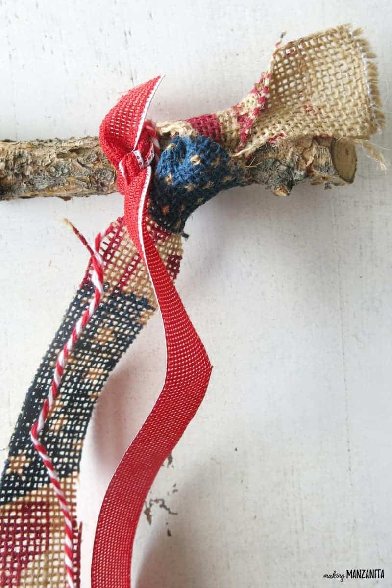 shows an up close picture of he burlap and red ribbon tied to a branch against a white table