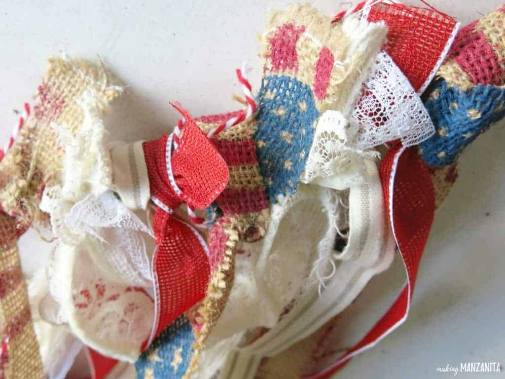 shows an up close view of the multiple knots of red, white, blue, and burlap ribbon tied