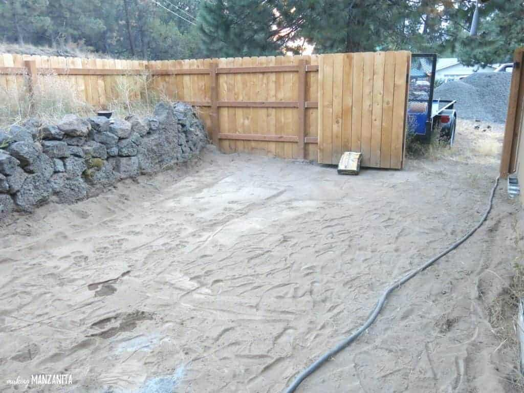 Flat and empty dirt ground  surrounded with rock bed and wood fence and open gate before wood garden beds were installed