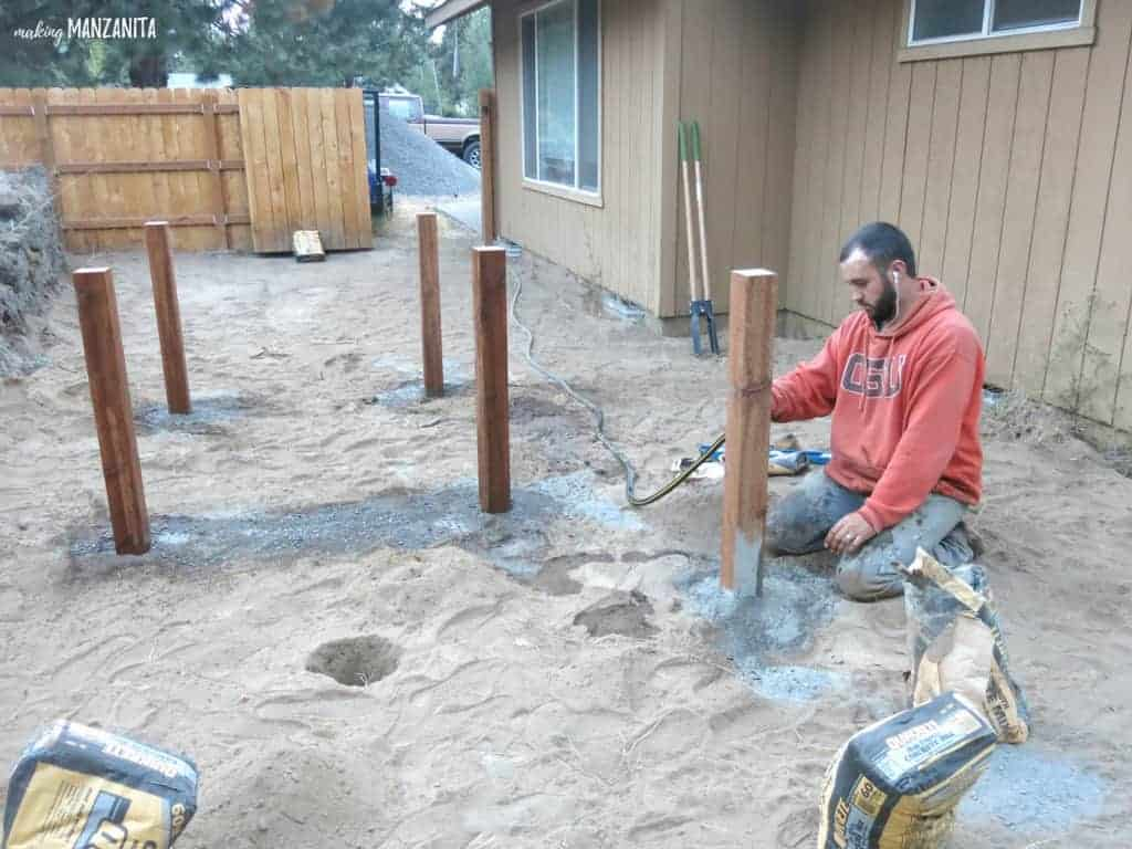 Posts in ground for the corners of garden beds. Man with hose wetting down concrete on the posts