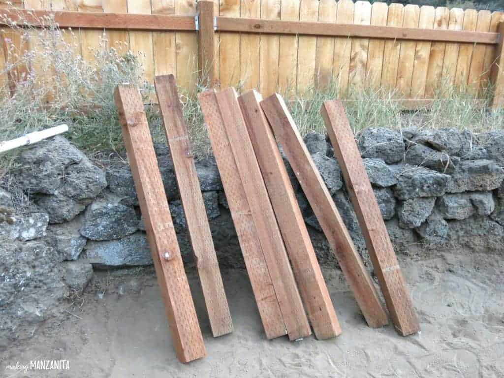 wood posts to be used as a corner supports for waist high raised garden beds leaning on the rock bed and wooden fence