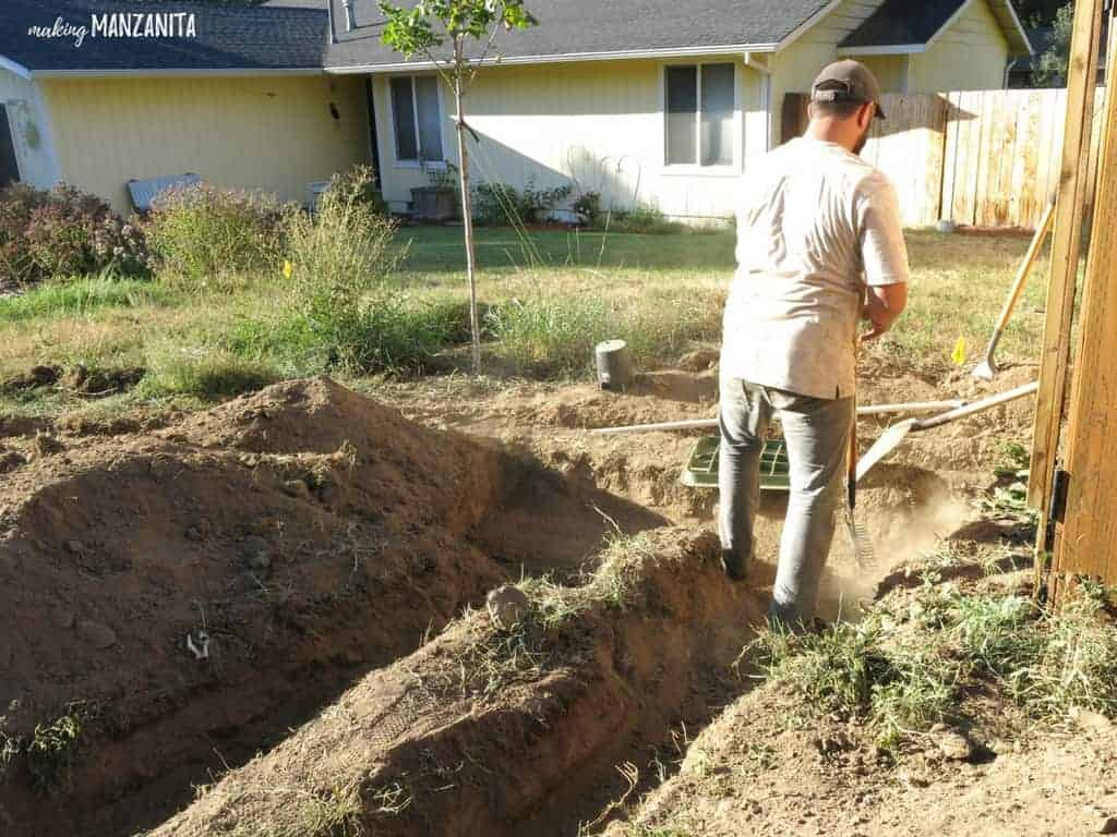 Man digging trenches for sprinkler system pipes