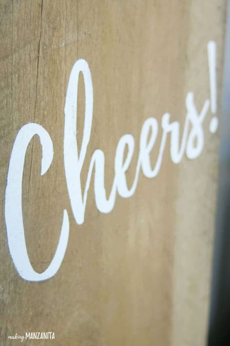 Zoomed in shot of Cheers in white lettering painted on reclaimed wood
