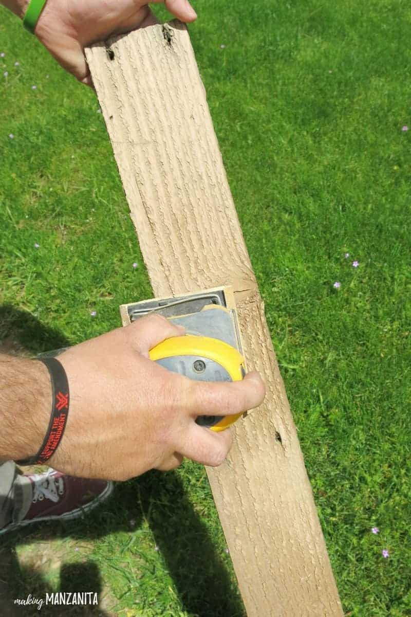 Man using a hand sander on a piece of reclaimed pallet wood to make wooden bottle opener