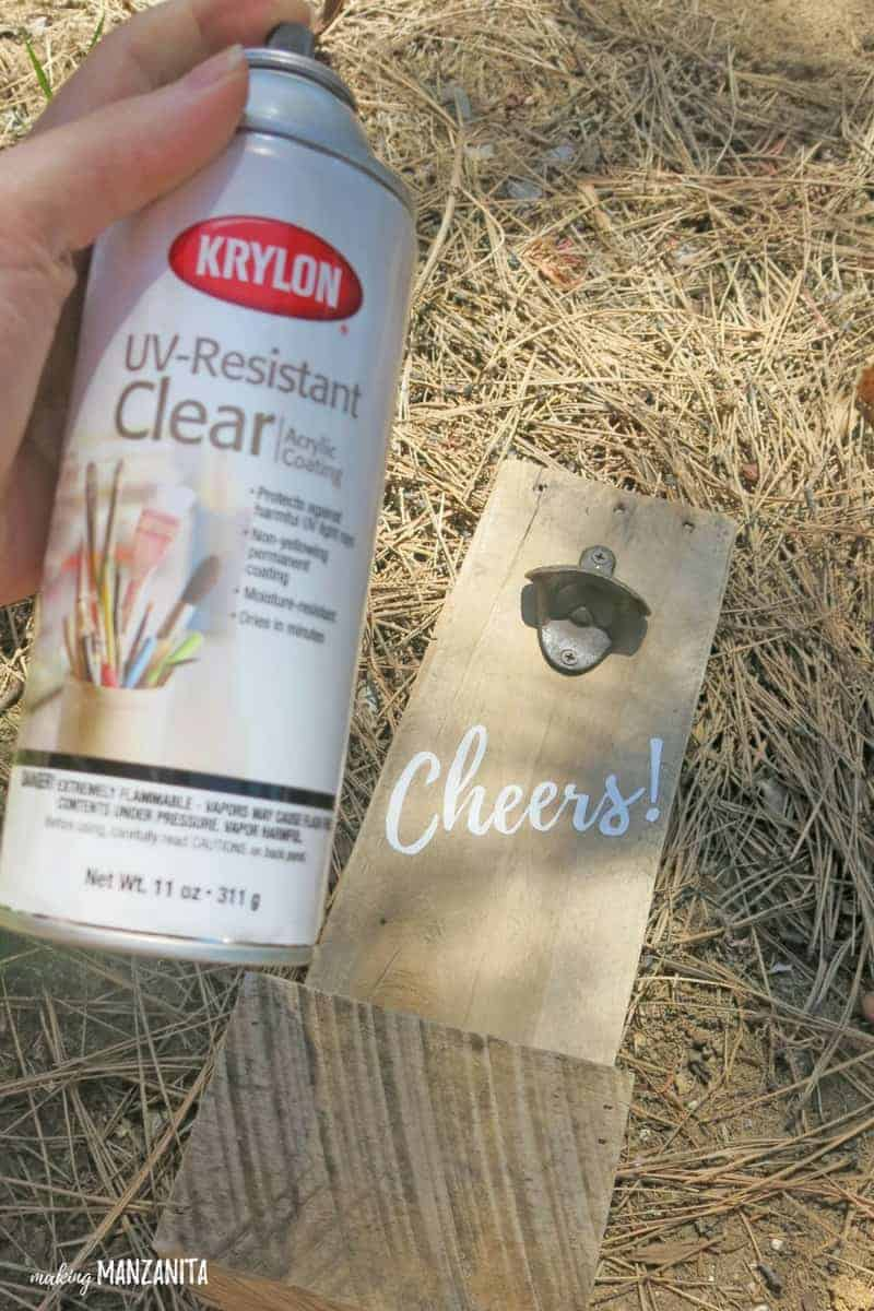 Spray bottle of Krylon UV-Resistant Clear acrylic coating in front of DIY bottle opener made with pallet wood and painted with Cheers on it