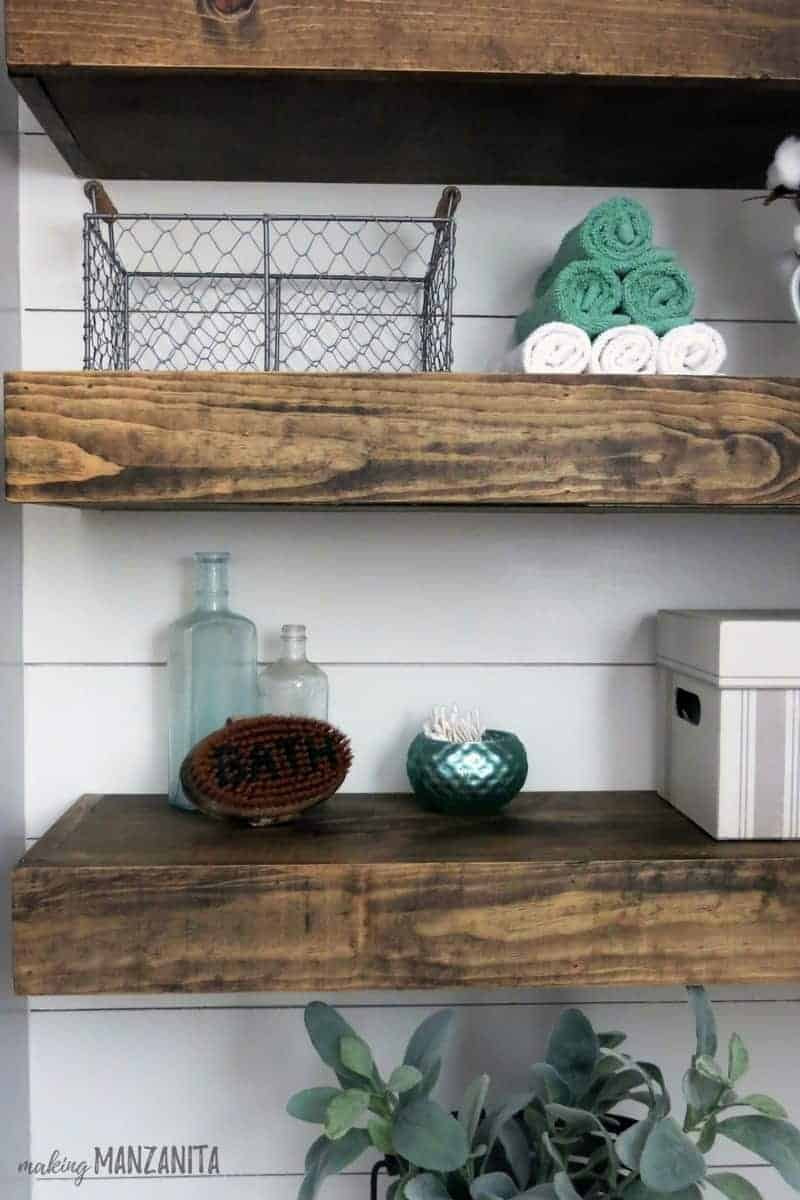 Wood shelves floating on shiplap wall decorated with farmhouse style in bathroom