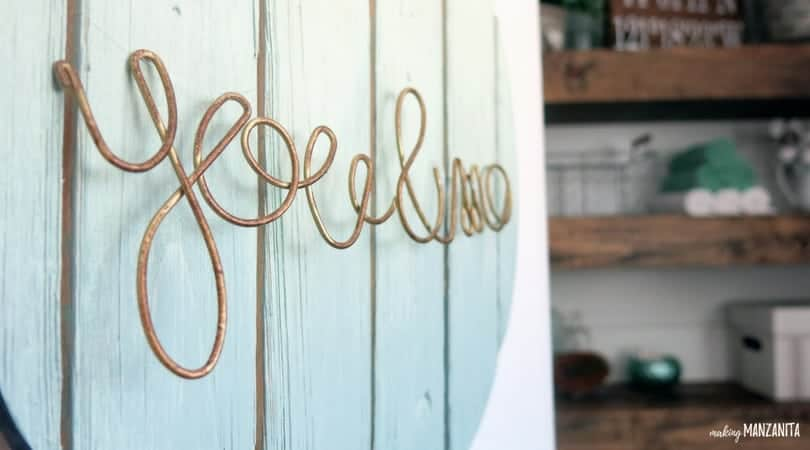 Close up shot of wood painted sign with wire letter hanging on it that say you & me, farmhouse styled shelves shown in background