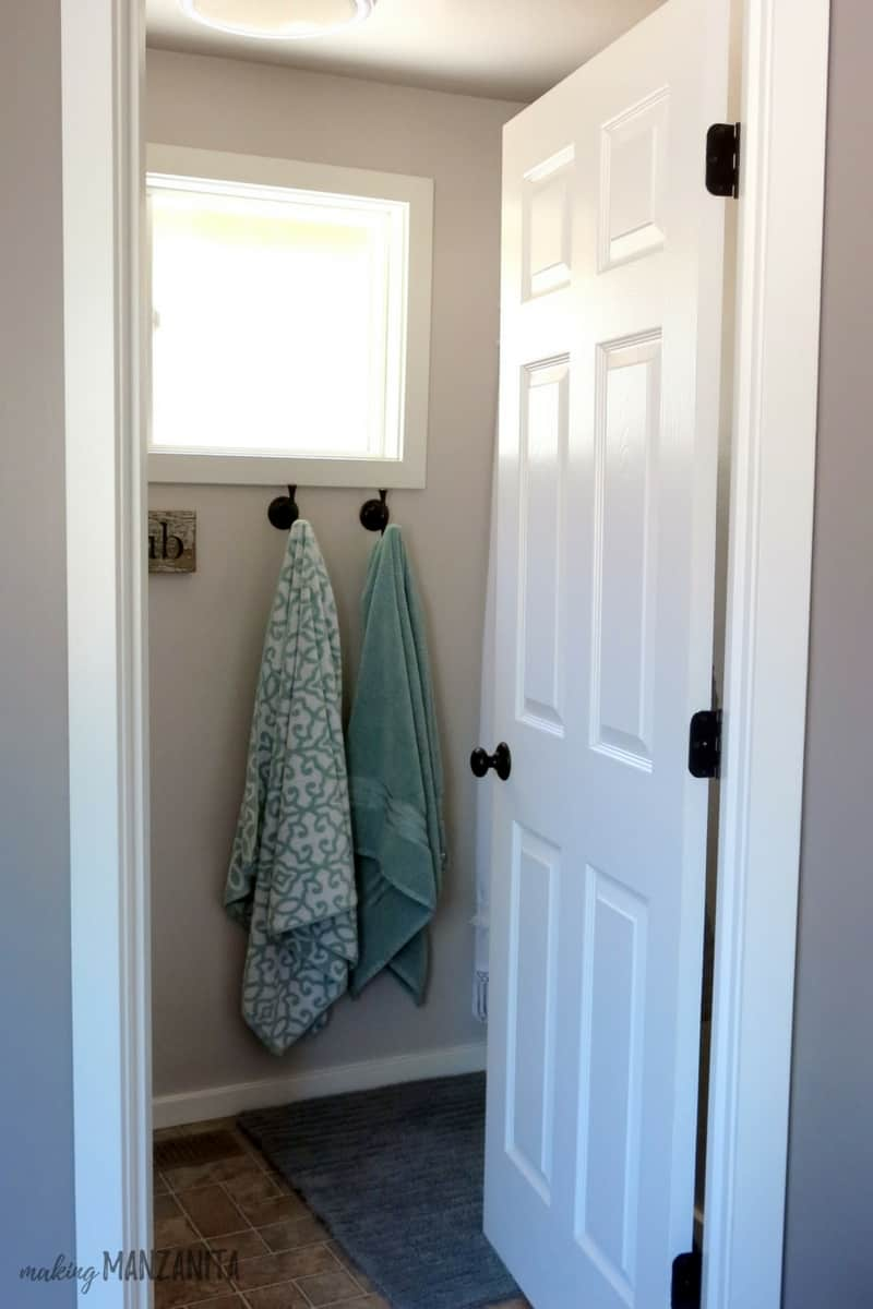 Front door of bathroom opened to see two towels hanging on hook under window