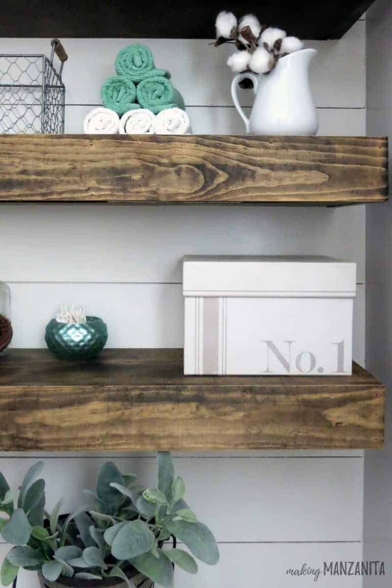 Floating shelves behind toilet for extra bathroom storage with farmhouse style
