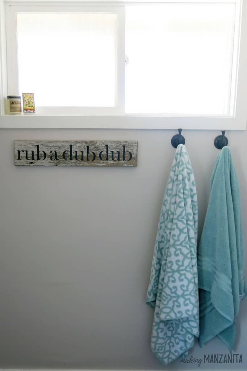 Gray wall painted with Burnished Clay by Behr in bathroom with towels hanging on hooks and rub a dub dub sign under window