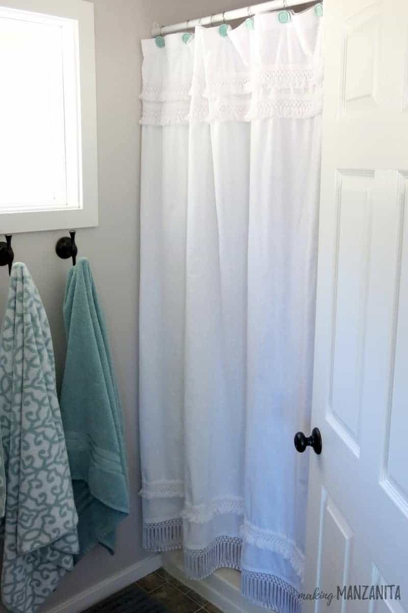 White shower curtain with macrame texture and boho style hanging up next to green towels on hooks