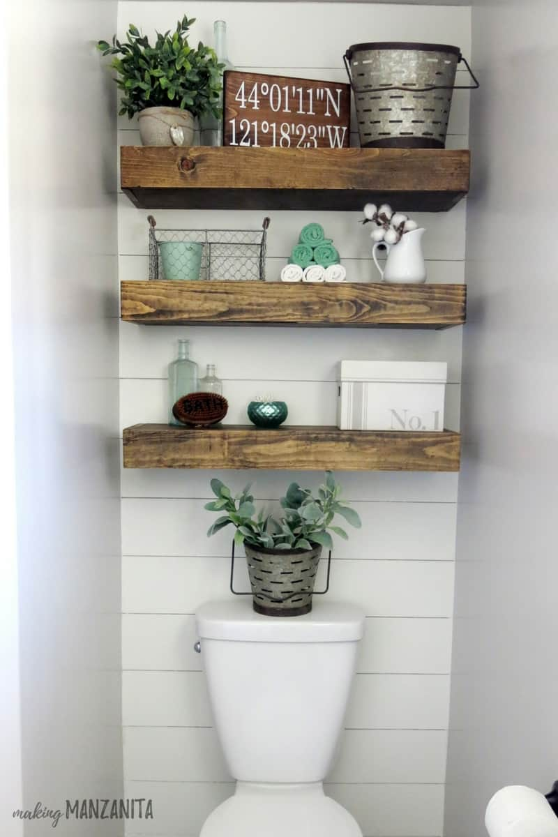 Bathroom shelves above toilet in a small bathroom with shiplap on the walls, wooden floating shelves decorated with farmhouse style