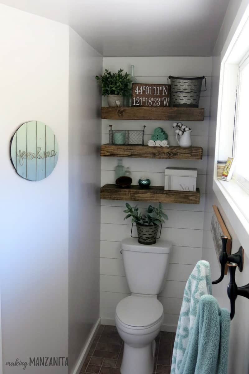 View of shiplap wall behind toilet with floating wooden shelves