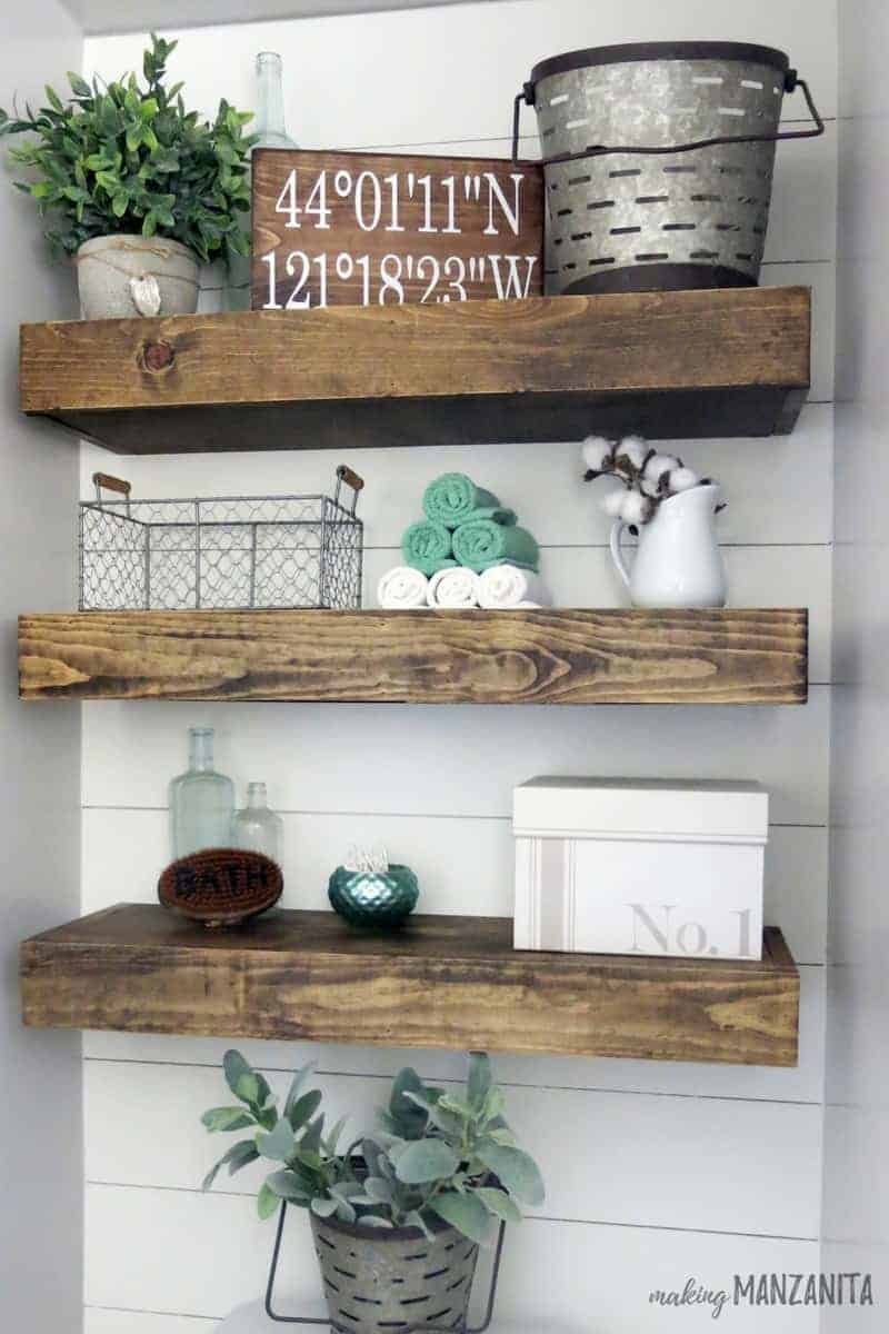 Wooden floating shelves hanging in farmhouse bathroom