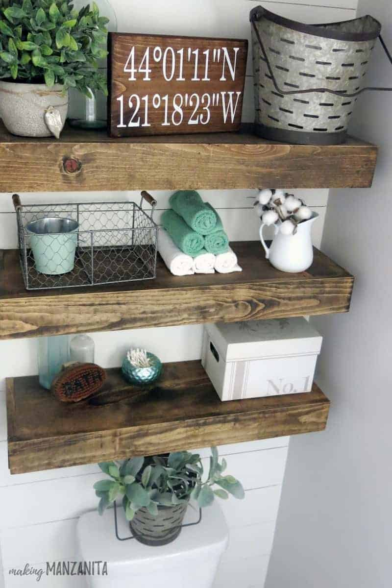 Floating wood shelving over toilet decorated with farmhouse style and pops of mint green
