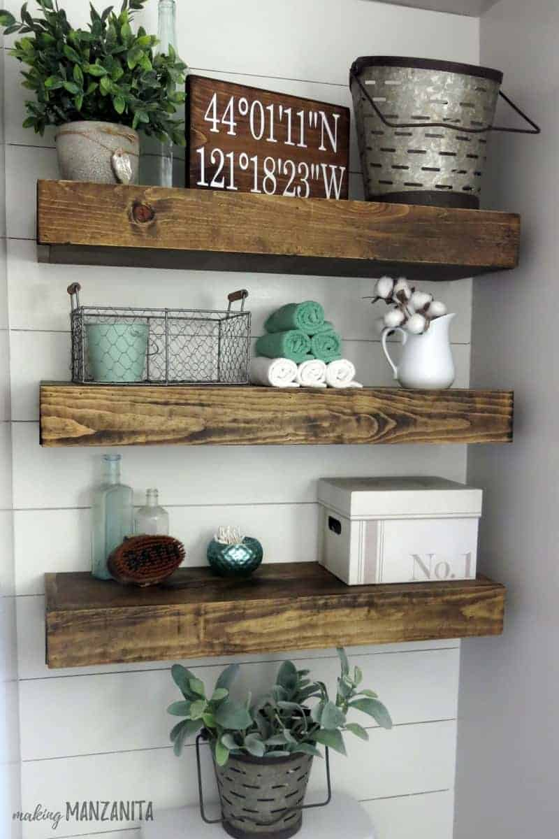 Shiplap wall with floating wood shelves decorated with farmhouse style, olive buckets, greenery, towels, cotton stems and storage