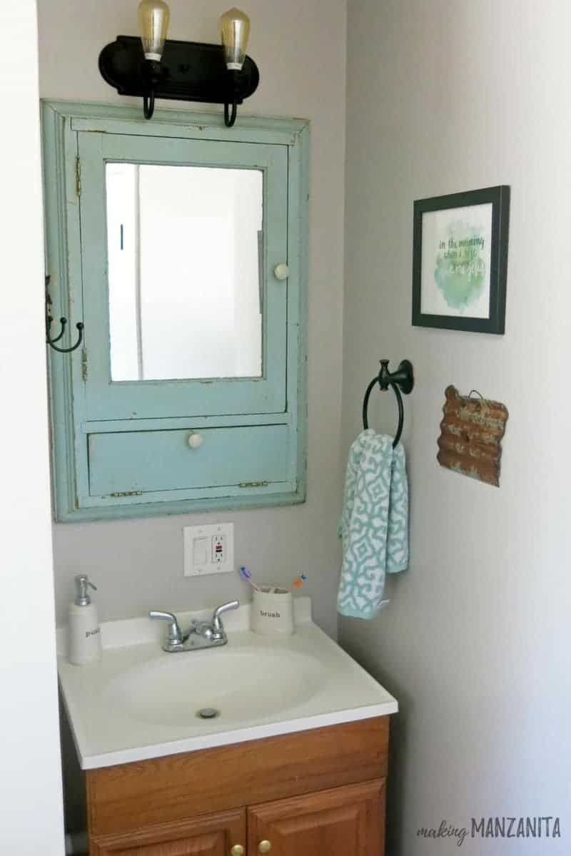 Mint green vintage medicine cabinet hanging above small vanity with black light and edison bulbs and towel ring