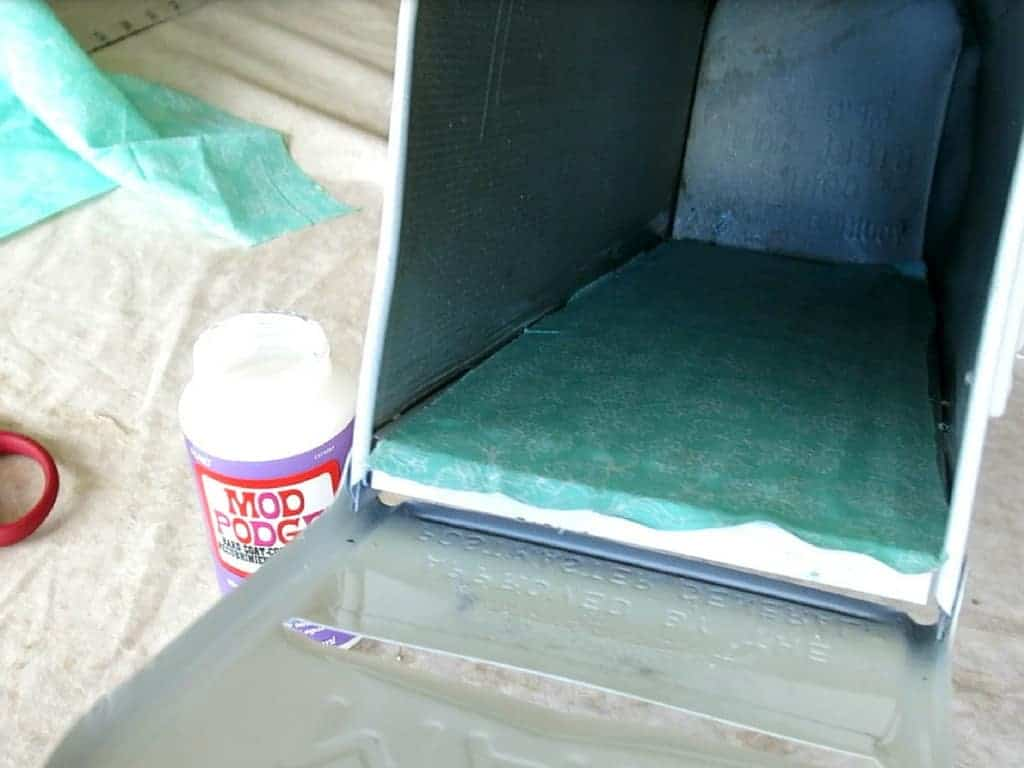 Inside view of the cleaned old mailbox beside a bottle of mod podge