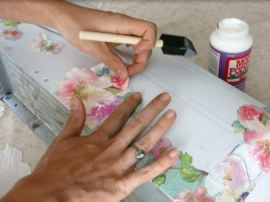 Attaching the cut flowers into the cleaned metal mailbox with mod podge