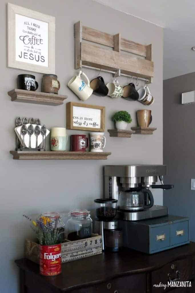 Vintage dresser being used as a coffee bar with wall shelves and hooks above it for mug storage with gray painted walls with Fashion Gray paint color from Behr Paint