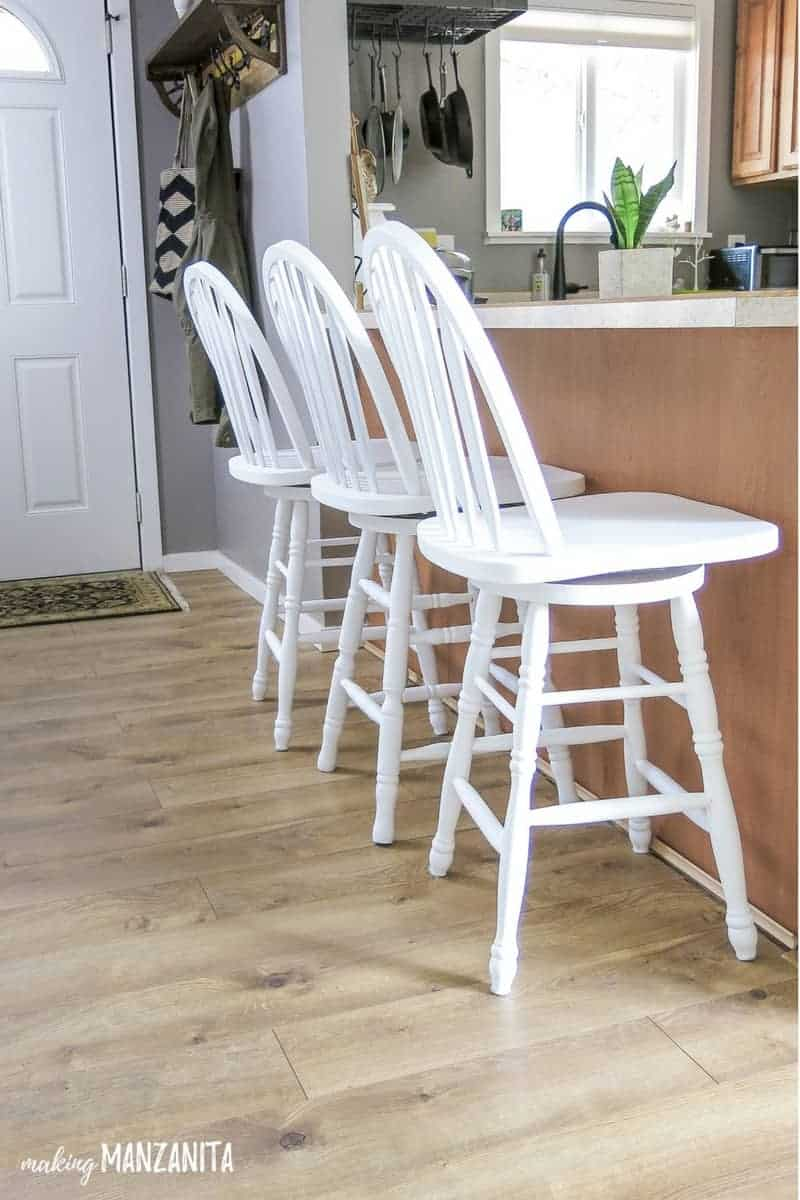 Three white painted barstools sitting next to each other at a kitchen bar