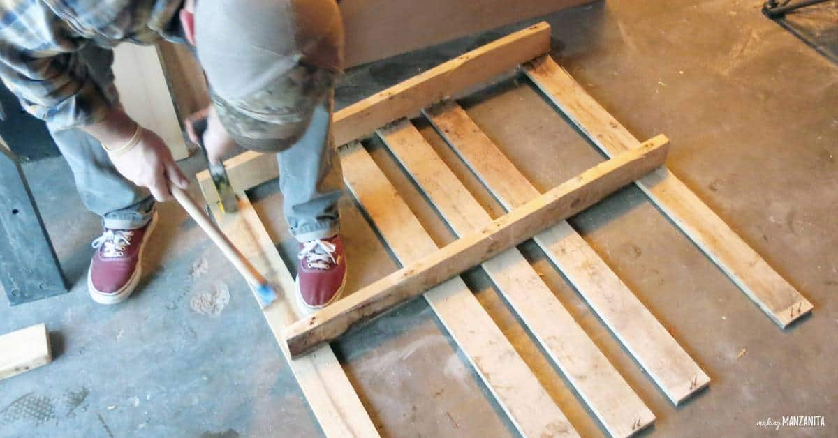 Using crow bar and hammer to take apart pallets for pallet wood furniture.