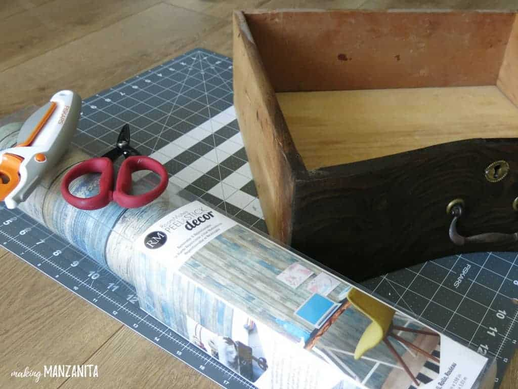 Supplies needed for adding peel and stick wallpaper to the sides of dresser drawers.