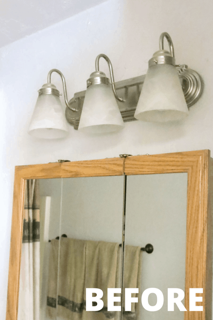 White and silver light fixture above the farmhouse vanity mirror before the spray paint light fixture makeover