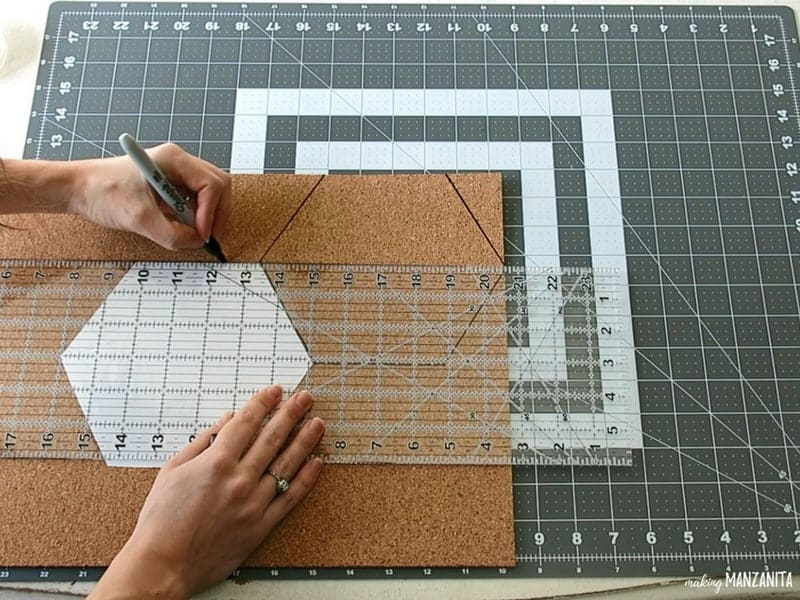Woman holding a marker and ruler tracing the hexagon shape on the cork board