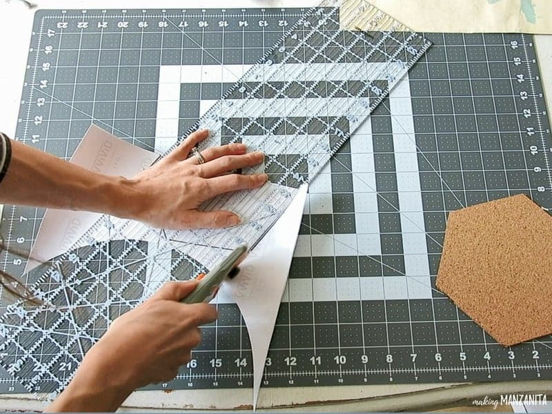Woman cutting a marble contact paper with rotary cutter and ruler and hexagon cork board beside it