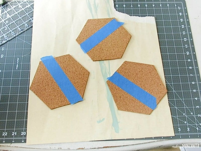 Hexagon cork boards with painter's tape taped off the top to color block paint the cork