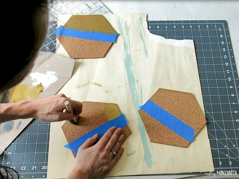 Woman holding a paint brush painting a hexagon cork board with gold acrylic paint while holding the other