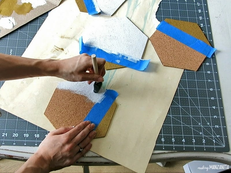 Woman holding and painting one hexagon cork board beside the two other hexagon cork board on top of the paper and cutting mat