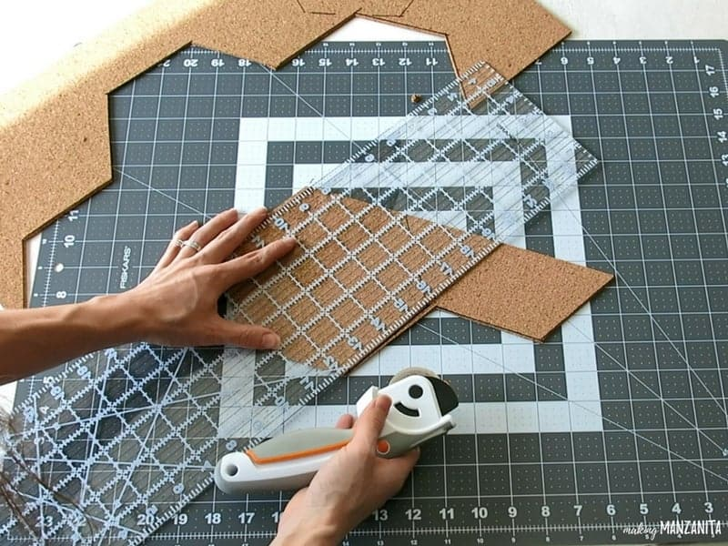 Woman holding a clear acrylic ruler and rotary cutter cutting the cork board into hexagon shapes for DIY hexagon cork boards