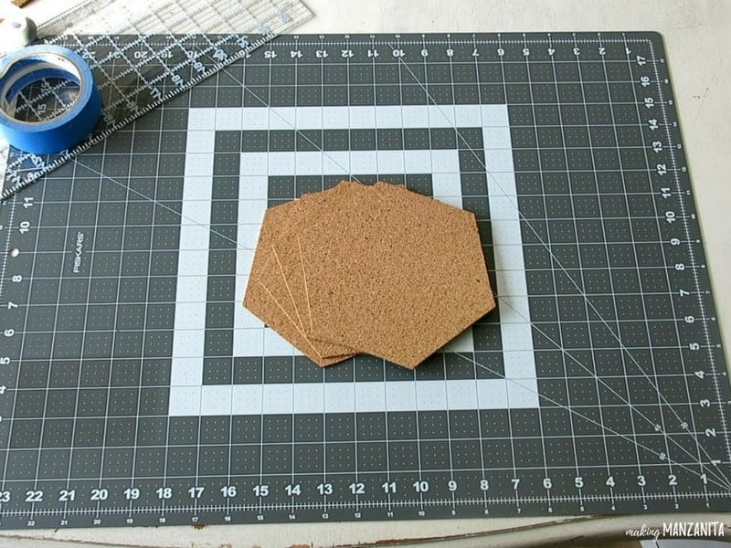 Cork board cut into hexagon shapes on top of the cutting mat with ruler and painter's tape beside it