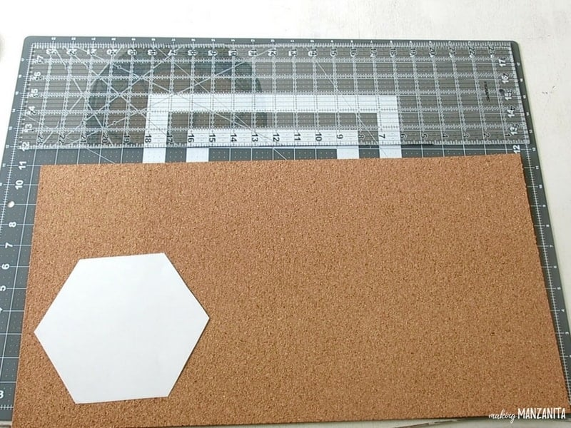 Hexagon printed and cut out of white copy paper placed on top of cork sheet and cutting pad with measurements before cutting cork to make DIY hexagon memo boards