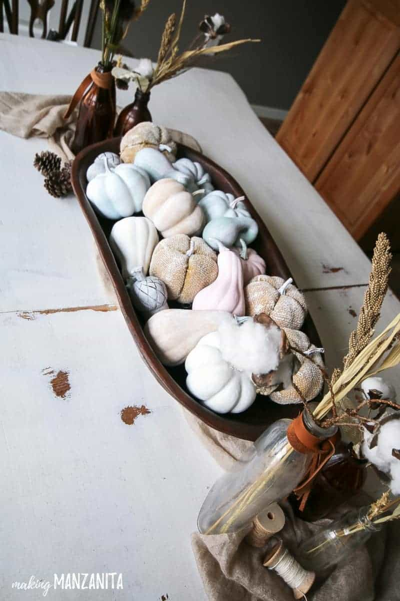 View of rustic table decorations for fall with painted mini pumpkins in farmhouse style wooden bowl and vintage bottles