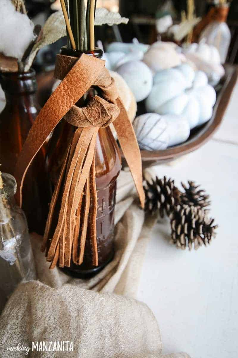 Vintage amber glass bottle with leather tied around the top and pine cones laying nearby on white table with painted mini pumpkins in background