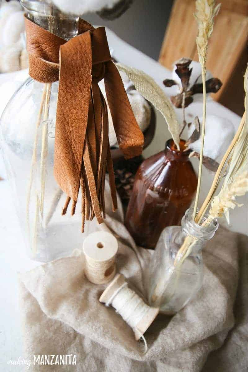 Vintage bottoms with leather wrapped around the tops with wheat in them on top of tan fabric with spools of natural twine to decorate a table for fall with farmhouse style