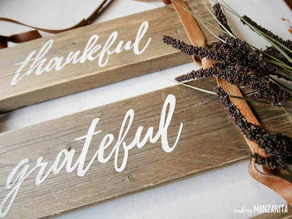 Close up view of leather sign lying on the table with dried grass on the side