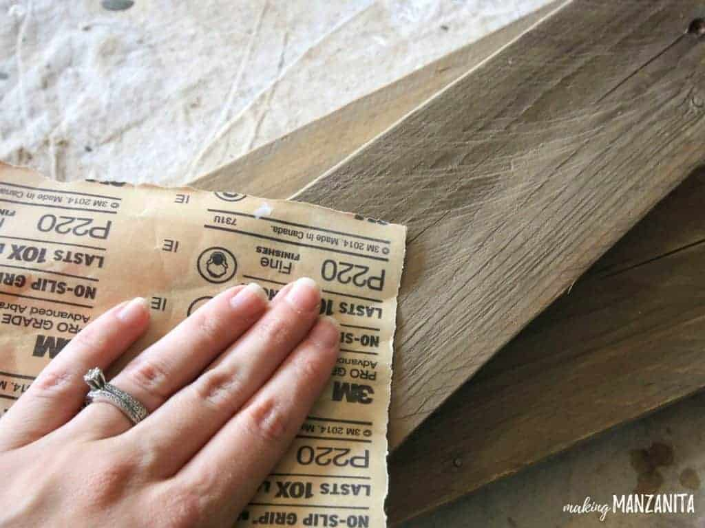 Hand of woman wearing ring sanding the pallet wood for leather fall sign with sand paper