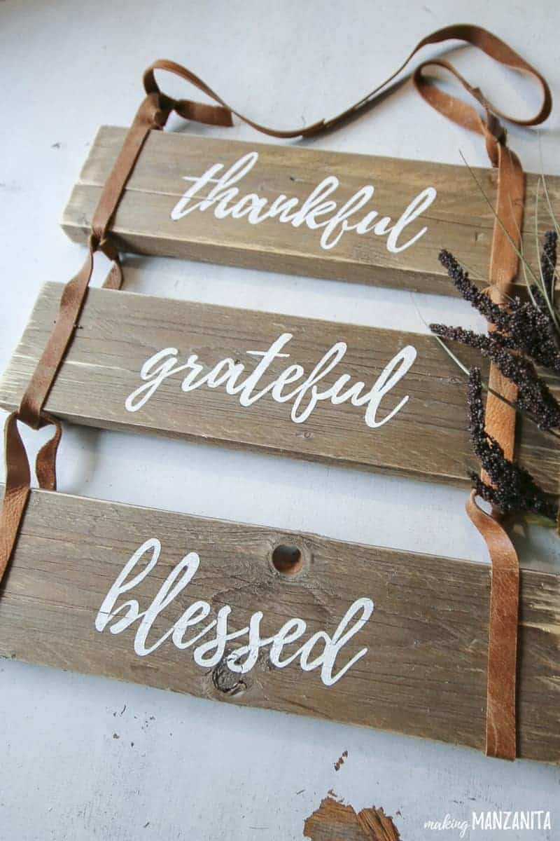 Close up of the rustic leather sign that says thankful grateful blessed and dried grass on the side
