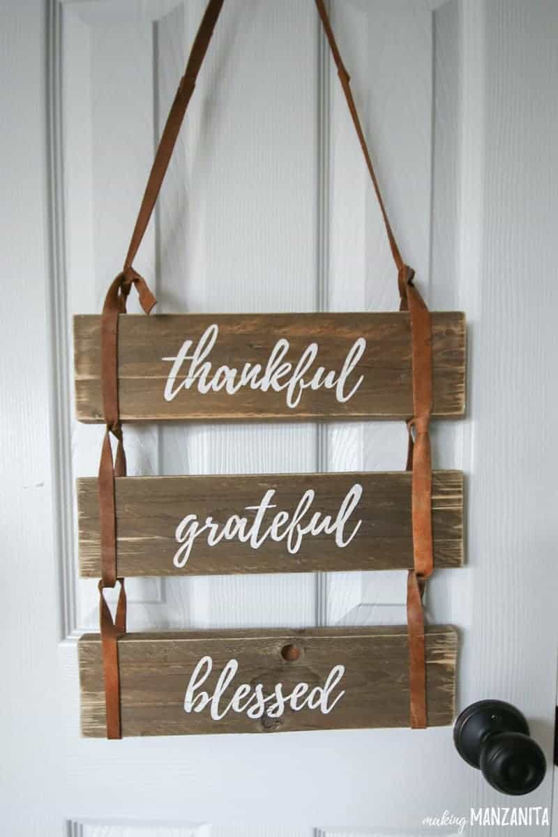 Close up view of leather sign with painted words that says thankful grateful blessed