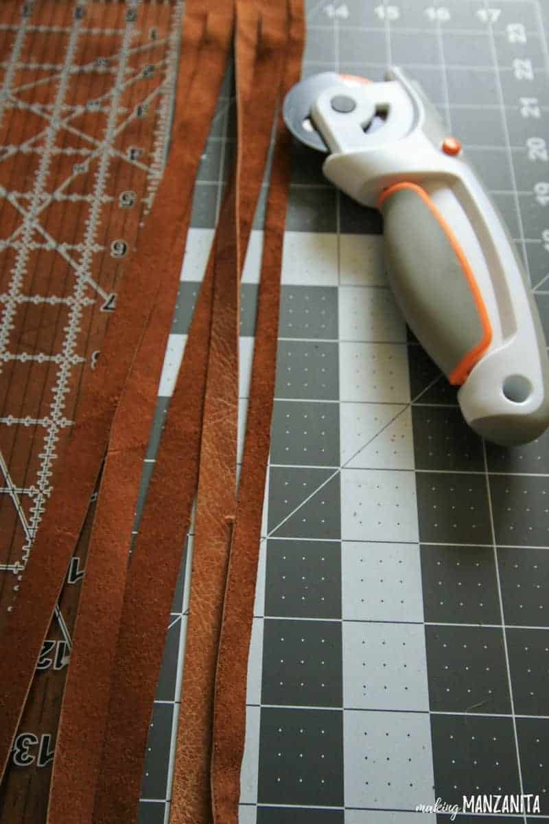 Leather strips and rotary cutter lying on cutting mat before adding to wood sign